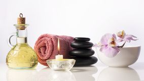 Zen spa stones next to towel, burning candle, bottle with oil and bow with flower. Spa still life composition. With space for text royalty free stock photos