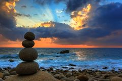 Nature Seascape with Zen Stacked Rocks on Beach at Colorful Sunrise royalty free stock photo