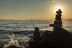 Zen Staplungssteine und Sonnenaufgang auf dem See stützen unter Stockbilder