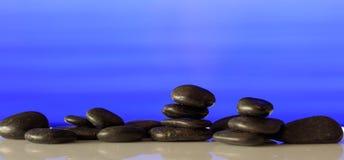 Zen stones row on blue background. Zen stepping stones on blue background with copy space Royalty Free Stock Image
