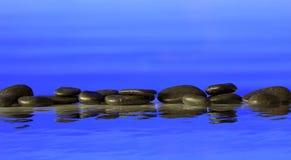 Zen stones row on blue background. Zen stepping stones on blue background, reflections on the water Royalty Free Stock Photo