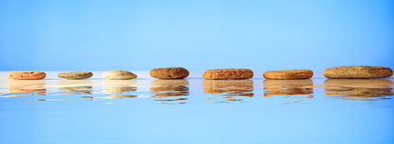 Zen stones row on blue background. Zen stepping stones on blue background, reflections on the water Royalty Free Stock Images