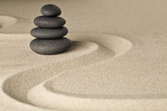 Zen stone balance and harmony. A pile of dark black stones stacked in a Japanese sand garden Stock Photography