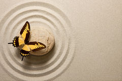 Zen stone with butterfly. Butterfly sitting on a rock surrounded by sand ripples Royalty Free Stock Photo