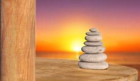 Zen stone like symbol of health and harmony with sun down beach. Background Stock Photo