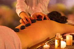 Zen stone massage. Girl on towels with masseuse and candles stock photo
