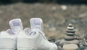 Zen Stone Meditation. Zen stone pyramid built around standing sports shoes. Sport and meditation together. Good sport pure thoughts and self-control Royalty Free Stock Photo