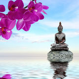 Zen stone,orchid flowers and Buddha reflected in water. Zen or Feng-Shui background-Zen stone,orchid flowers and Buddha reflected in water Stock Photo