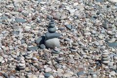 Zen stone pyramids among beach pebbles royalty free stock photos