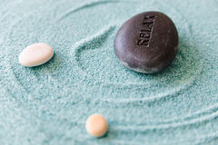 Zen Stone Relax. Stone with a sign Relax on a sand, zen stones, sand therapy, meditation Royalty Free Stock Photography