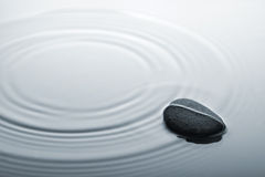 Zen stone in rippled water Royalty Free Stock Photo