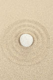 Zen stone in sand with circles Royalty Free Stock Images