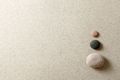 Zen stones. Three colorful zen stones at right side of sand background Stock Photos