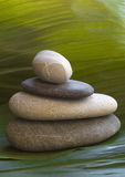 Zen stones. Vertical composition of some stacked stones. Leaf background royalty free stock photo