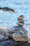Zen stones against blue sea bokeh Stock Images