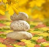 Zen stones of Autumn leaves. Three Buddhist Zen stones balancing on Autumnal Maple leaves Royalty Free Stock Image
