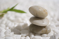 Zen stones and bamboo. On white pebbles background - meditation concept royalty free stock photo