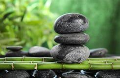 Zen stones on bamboo against background. Zen stones on bamboo against blurred background stock images