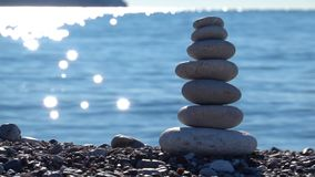 Zen stones on beach for perfect meditation. Calm zen meditate background with rock pyramid on sand beach symbolizing