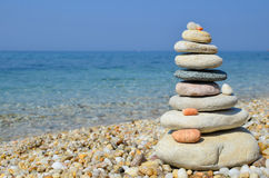 Zen stones on a beach. Stack of multicolored zen stones on a pebble beach, Greece, horizontal orientation stock image