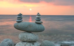 Zen stones on beach at sunrise Royalty Free Stock Image