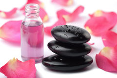 Zen stones, essential oil and rose petals isolated Royalty Free Stock Photo