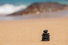 Zen stones jy on the sandy beach near the sea. Royalty Free Stock Image