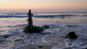 Zen stones in the morning day at the seashore with waves.  stock video footage