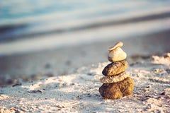 Zen Stones na praia para a meditação perfeita O zen calmo medita o fundo com a pirâmide da rocha na praia da areia que simboliza  Foto de Stock