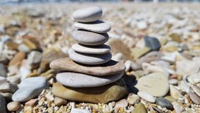 Zen stones for relaxing moments. Relaxing moments in nature. Sun light, fine sand, waves sound and peace Royalty Free Stock Photos