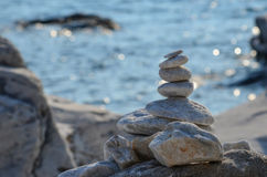 Zen stones on rocky beach. Before sunset against blue bokeh background royalty free stock photos