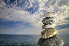 Zen stones on sea and cloudy sky background. Royalty Free Stock Photo