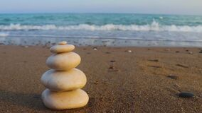 Zen stones and sea waves. The concept of harmony, stability, life balance, relaxation and meditation. A pyramid of stones on the s