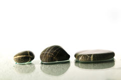 Zen stones with splashing  water drops. Isolated wet zen stones with splashing  water drops  representing concept of natural balance and perfect harmony Royalty Free Stock Image