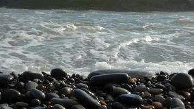 Zen stones stack on the beach breaking by sea surf stock video