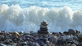 Zen stones stack on the beach with sea surf behind.