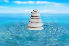Zen stones stack from large to small in water with circular wave. S and blured sky Stock Image