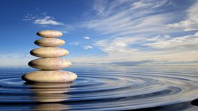 Zen stones stack from large to small  in water Royalty Free Stock Photo