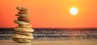 Zen stones stack on sea background at sunset royalty free stock photo