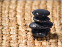 Zen stones stacked on a grass matte. At day spa Royalty Free Stock Image