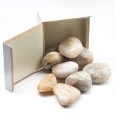 Zen Stones in una scatola su un fondo bianco Fotografie Stock