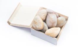 Zen Stones in una scatola su un fondo bianco Immagine Stock Libera da Diritti
