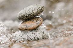 Zen stones in water. Stacked Zen stones in the water with drops splashing Stock Images