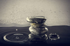Zen stones in the water. Zen stones in the water with splashing drops. Horizontal image Royalty Free Stock Image