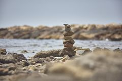 Zen symbol: stack of rocks on the beach. Zen symbol of peace and meditation: stack of rocks with the background of a rocky beach and the sea Royalty Free Stock Image