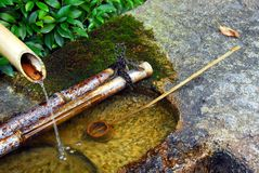 Zen water basin. Stone water basin, bamboo pipe and ladle at Ryoanji temple, Kyoto, Japan stock photography