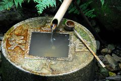 Zen water basin. Stone water basin, bamboo pipe and ladle at Ryoanji temple, Kyoto, Japan stock images
