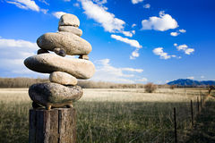 Zen western style. Stones balancing on a fencepost in rural Montana Stock Photo