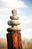 Zen western style. Stones balanced on old painted fence post in rural Montana Stock Photography