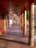 Zen: wooden walkway with disc gong. Wooden cedar walkway with disc gong at buddhist meditation center in winter Royalty Free Stock Images